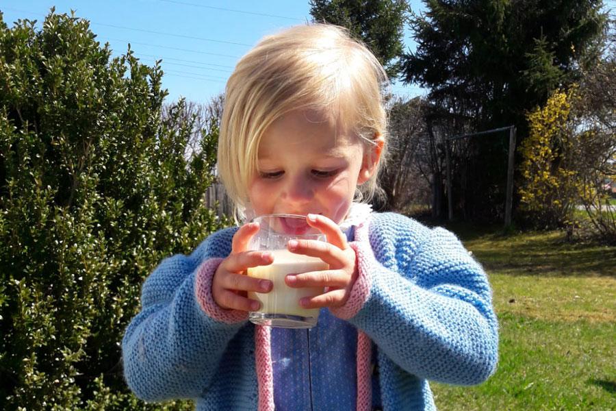 Kleines Mädchen mit frischer Milch